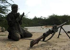 A hard-line Somali Islamist prays near a roadblock
